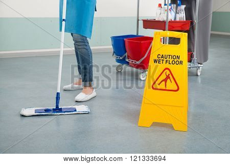 Female Janitor Mopping Corridor With Caution Sign