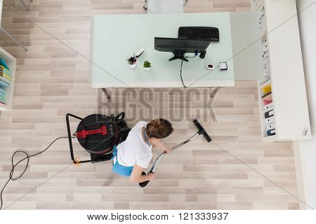 Female Janitor Cleaning Wooden Floor With Vacuum Cleaner