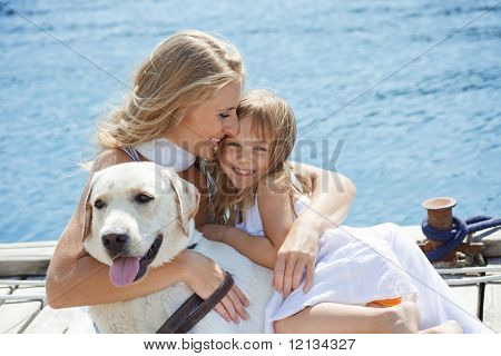 Happy family playing with dog on berth near sea in summer