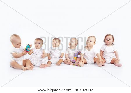 Group of babies sitting on white studio background