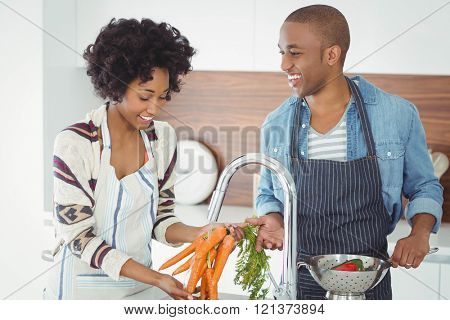 Happy couple washing vegetables in the kitchen