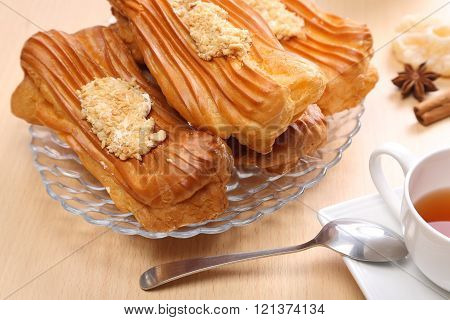 Eclair is a French dessert in the form of an oblong cake choux pastry with scalded cream poster