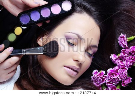 Make-up artist making eye visage to beautiful woman poster