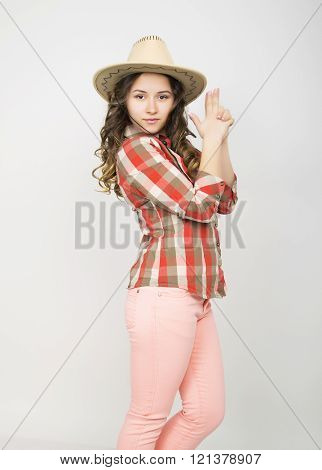 beautiful curly girl in pink pants, a plaid shirt and cowboy hat. depicts a hand gun