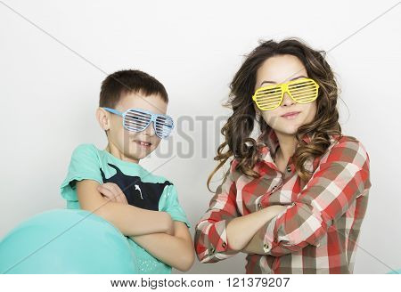 brother and sister, wearing glasses in the style of disco. fold one's arms
