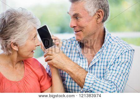 Happy senior couple listening to smartphone on the sofa