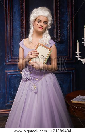Woman in historic baroque style dress with a book in their hands