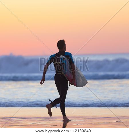 Silhouette of surfer on beach with surfboard.