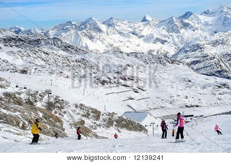 People Skiing In European Alps. Scenic View.