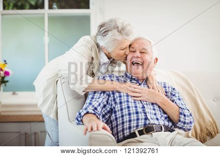 Senior woman embracing man in living room poster