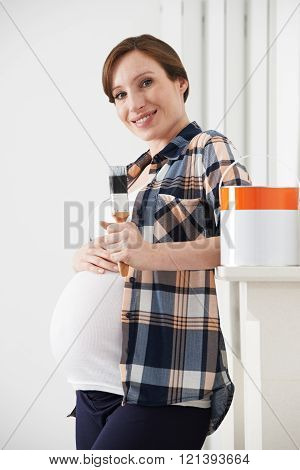 Pregnant Woman Taking Break Whilst Decorating Nursery