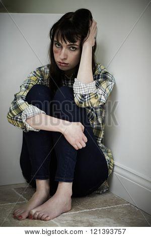 Female Victim Of Domestic Abuse Sitting On Floor