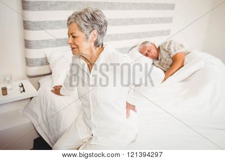 Senior woman suffering from backache sitting on bed in bedroom