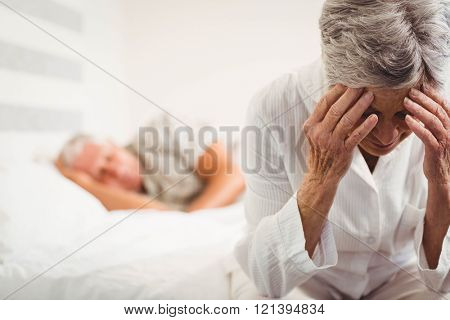 Frustrated senior woman sitting on bed in bedroom