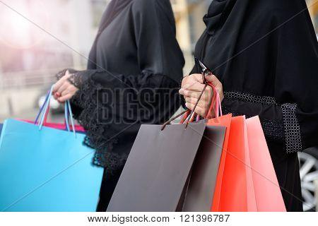 Emarati Arab women coming out of shopping in Dubai United Arab Emirates.