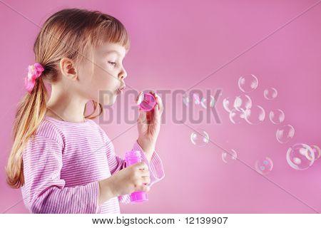 Retrato de menina linda engraçada soprando bolhas de sabão