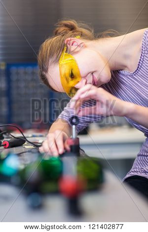Female scientist carrying out research experiments in a quantum optics lab (color toned image)