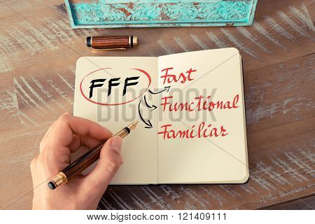 Retro effect and toned image of a woman hand writing a note with a fountain pen on a notebook. Acronym FFF as Fast, Functional, Familiar as business concept image