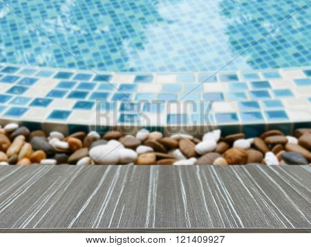 Empty Wooden Table With Stone On The Edge Of The Swimming Pool Blur Background