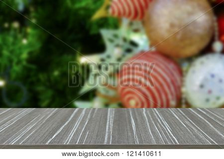 empty wooden table with christmas tinsel ornament decorating on christmas tree blur background