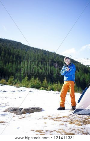 A Tourist Stands Near A Tent And A Backpack.