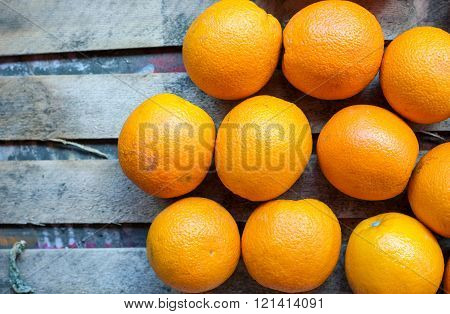 Orange fruit on rustic wooden background oranges on market stall top view close-up. Selective focus.