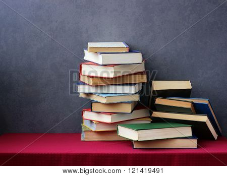 A Stack Of Books On The Table With A Red Tablecloth.