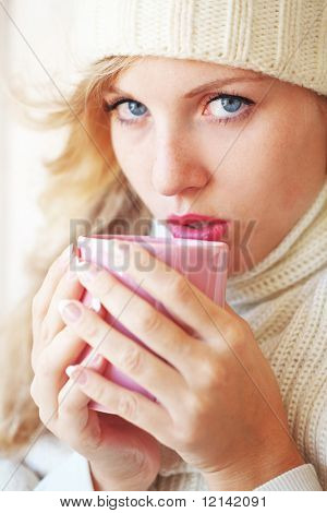 Young beautiful woman wearing winter clothing drinking hot coffee