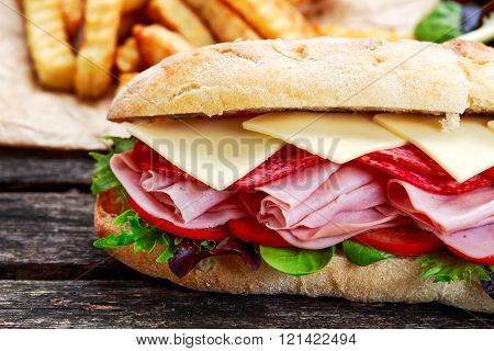 Sandwich with lettuce, slices fresh tomatoes, salami, hum and cheese