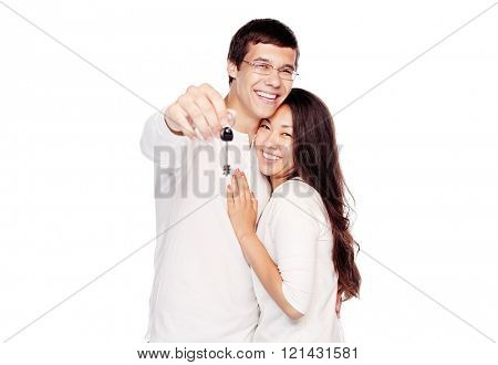 Lovely interracial couple, hispanic man and asian girl, showing key of their new house, hugging and smiling isolated on white background - real estate for young family concept