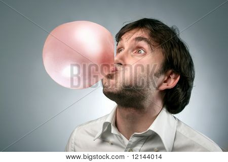 A man blowing in a chewing-um