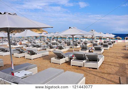 Mykonos, Greece - May 28, 2015: Empty sun beds on morning beach on greek island mykonos, greece, with only few people on the beach, Mykonos, in May 2015