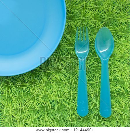 Background With Blue Plate And A Fork And A Spoon On The Green Grass