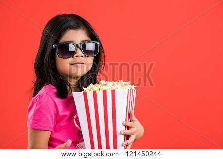 happy girl eating popcorn and wearing glasses, indian girl eating popcorn,
