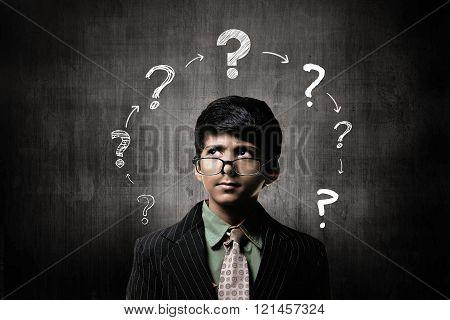 Confuse Little Boy Wearing Glasses, Thinking Near Chalkboard