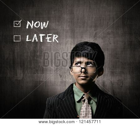 Cute Intelligent Little Boy Wearing Glasses On Nose Thinking While Standing Before A Chalkboard. Thinking Now Or Later