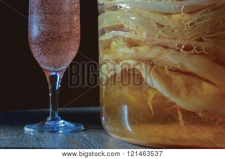 Close up of a jar filled with scoby cultures ready to start a new batch and a champagne glass filled with the finished bubbly product.