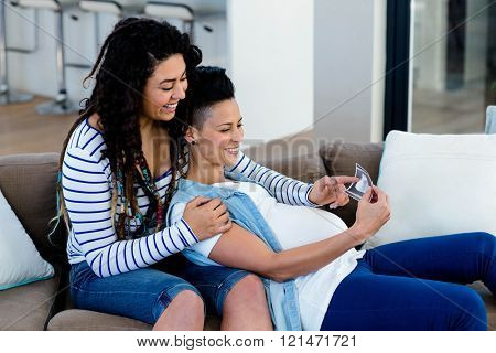 Pregnant lesbian couple sitting on sofa and looking at sonography report
