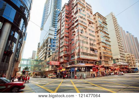 HONG KONG, CHINA - FEB 7: Wide broad street with skyscrapers and fast driving taxi car on city road on February 7, 2016. Hong Kong dollar is the eighth most traded currency in the world.