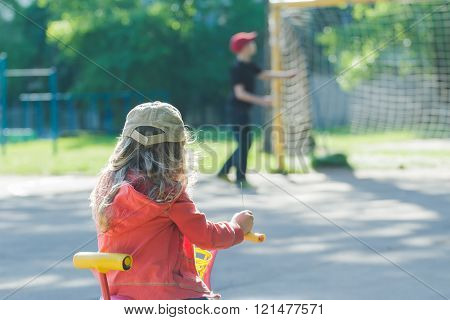 Back view of little girl looking at playing boy on kids street football ground