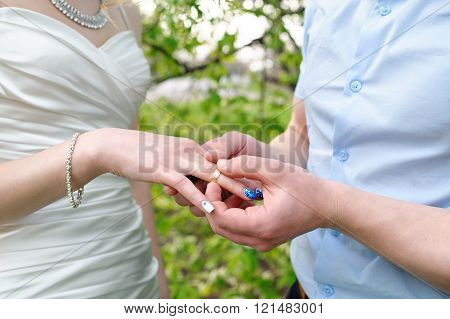 bride groom dresses a wedding ring on her finger