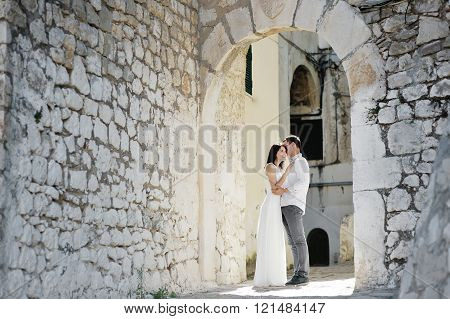 Happy Couple Bride And Groom Tenderly Embraced In Wedding Day In Sperlonga, Italy