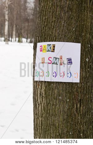 A paper ad with the phrase: Take a Smile and with smile signs