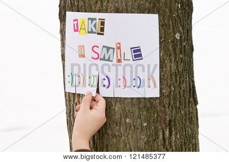 Human hand keeps for paper ad with the phrase: Take a Smile and with smile signs.