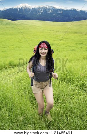 Woman hiking mountain and walk on meadow