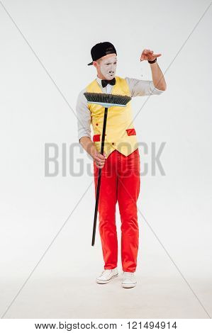 studio shot of mime with a mop in his hands isolated on a white background