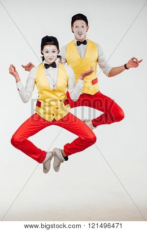 studio shot of two mimes jumping isolated on a white background
