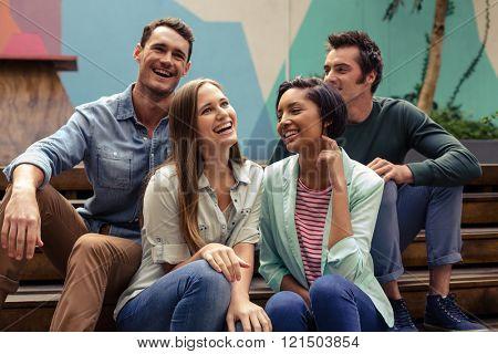 Happy friends talking outside the bar