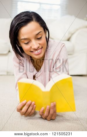 Smiling brunette reading a book lying on the carpet