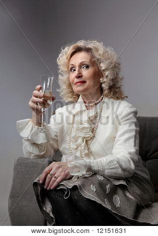 a senior Woman, trinken ein Glas Sekt